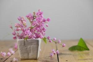 Still life with pink flowers on wooden table