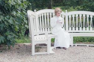 Tea drinking victorian woman sitting on garden seat. photo