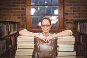 Profesora rubia de pie entre libros en la biblioteca