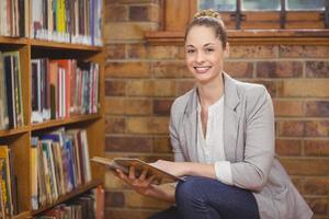 maestra rubia buscando libro en la biblioteca