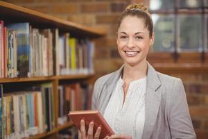 maestra rubia sosteniendo un libro en la biblioteca