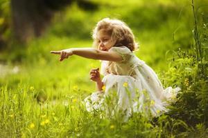 menina com uma flor indica algum lugar com a mão