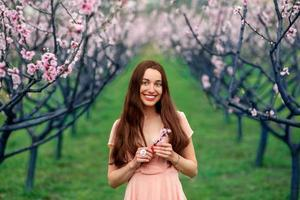 Woman enjoying spring in the green field with blooming trees
