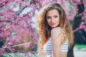 Hermosa mujer joven con hermosa feria rizada al aire libre, floración foto