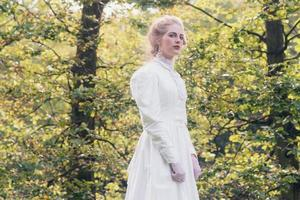 Retro victorian fashion woman in front of trees. photo