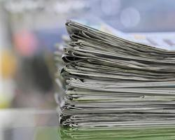 Stack of folded news papers on blurry background