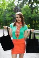 Hermosa chica con bolsas de tela caminando sobre un puente de madera