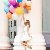 hermosa dama sosteniendo un montón de globos