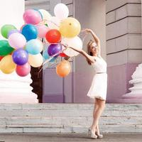 beautiful lady holding a bunch of balloons