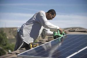 Man Working On Solar Panelling Rooftop