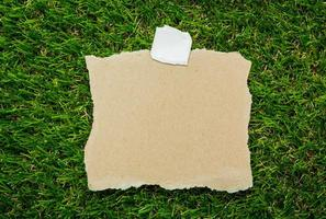 Blank recycled note paper on green grass background