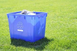 Papelera de reciclaje sobre la hierba verde foto