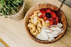 Sliced strawberries in brown wooden bowl