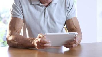 uomo anziano utilizzando tablet video