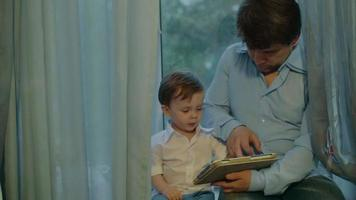 Vater und Sohn beobachten Cartoons in Tablette