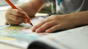 Kinderhände malt einen Buntstift auf ein Papier