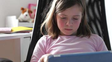 garota usando tablet digital no quarto video