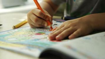 manos de niño pinta una naranja lápices sobre un papel
