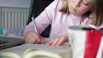 Mädchen macht schriftliche Hausaufgaben im Schlafzimmer