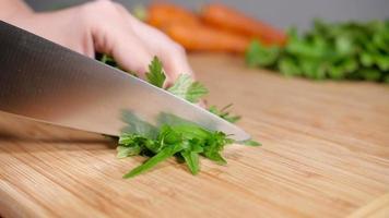 Couper le persil frais sur une planche à découper en bois video
