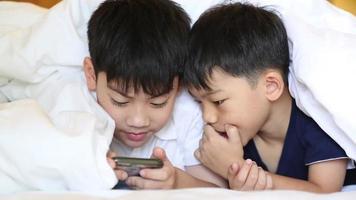 criança asiática está jogando no tablet, sorrindo, deitada na cama. video