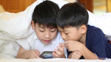 enfant asiatique joue sur tablette, souriant, allongé sur le lit.