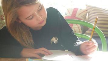 ragazza seduta al tavolo al chiuso a fare i compiti
