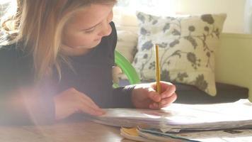 fille assise à table à l'intérieur à faire ses devoirs