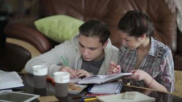 estudante do sexo masculino está escrevendo a tarefa.