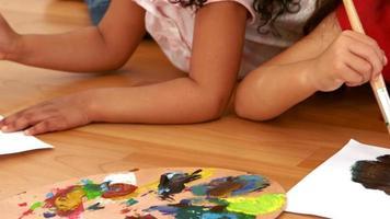 garotas deitadas no chão e pintando
