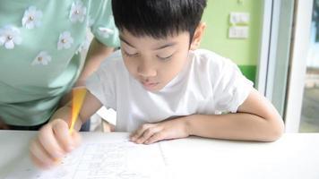 mãe asiática está ajudando o filho a fazer a lição de casa