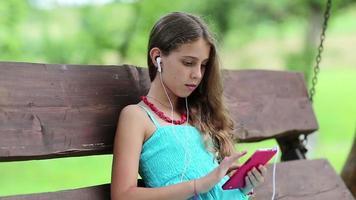 bella ragazza si siede sulla panchina altalena e utilizza lo smartphone rosso