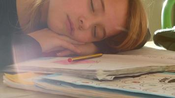 garota cansada dormindo com a cabeça deitada na lição de casa