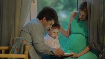 niño muestra algo en tableta a sus padres