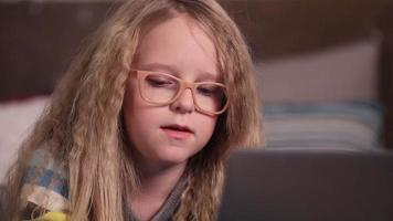 hermosa niña con computadora en el dormitorio video