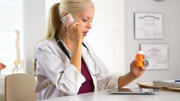 Doctor holding prescription pill bottle and talking on cell phone
