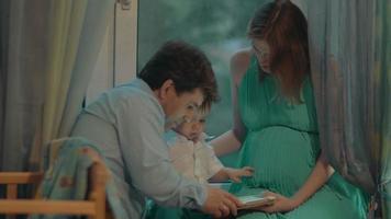 kleiner Junge hält Tablette und seine Eltern