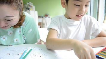 mãe asiática está pintando o filho para fazer o dever de casa
