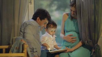 vereinte Familie, die das Tablett beobachtet