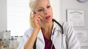 Ärztin, die auf dem Handy spricht
