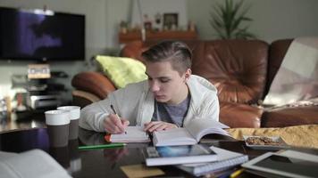 un apuesto estudiante escribiendo notas en el cuaderno.