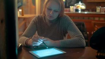 Mujer con tablet pc con lápiz óptico en cafe video