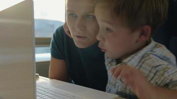 madre e figlio davanti al computer portatile in treno