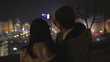 Young couple in love taking selfie and kissing at romantic date, night cityscape