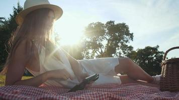 Young woman using tablet computer touchscreen on picnic video