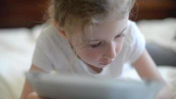 Little girl playing on the tablet pc. video