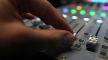A person working on a colorful audio mixer, he is pulling up the knobs