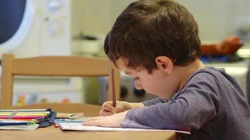 un simpatico ragazzino disegna al tavolo di casa