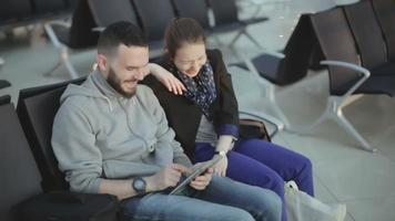 el chico y la chica en ropa casual miran la pantalla de la tableta y se ríen.