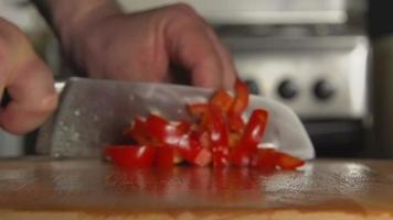 SLOW: A cook's hand cuts a bell pepper by a knife